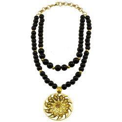 Collar corto doble negro con dije en zamak bañado en oro