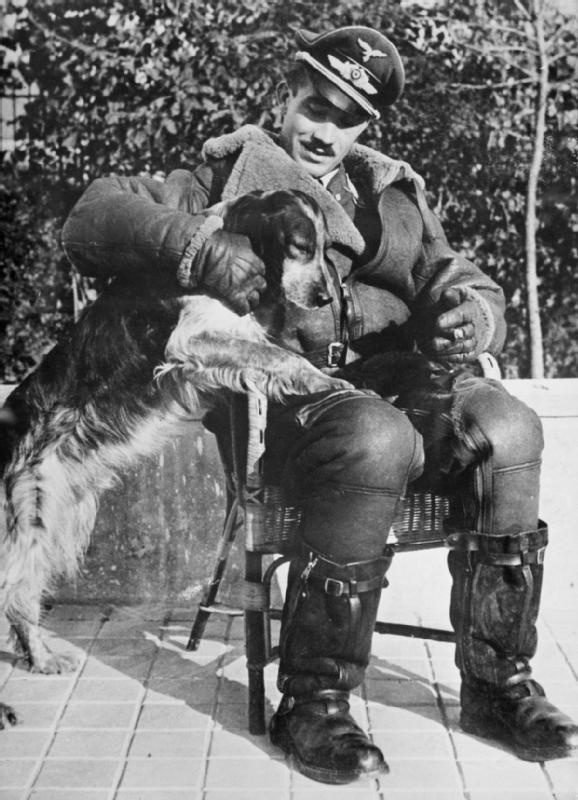 THE BATTLE OF BRITAIN 1940. German Personalities: Major Adolph Galland seated in a chair with his dog.