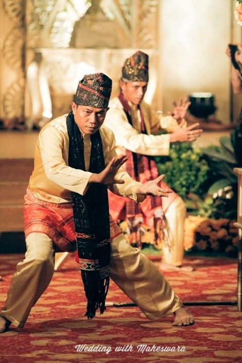 Penutup kepala pada pria penari dalam prosesi pemberian ulos kepada pengantin dengan pernikahan adat Batak Mandailing Sumatra Utara, memiliki warna dan motif berbeda dengan penutup kepala penabuh kendang.