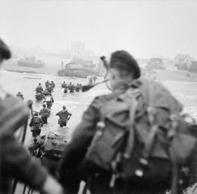 Sword Beach. On the right of the column, wades through the water. The figure in the foreground is Piper Bill Millin. By Evans, J L (Capt), No 5 Army Film & Photographic Unit - This is photograph B 5103 from the collections of the Imperial War Museums (collection no. 4700-29), Public Domain.