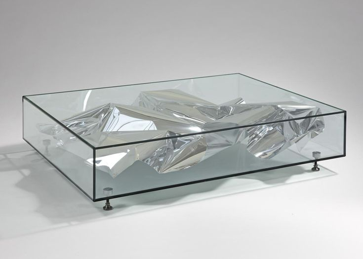 Crumpled sheets of metal appear to float inside or wrap around the low tables in a collection by design studio Fredrikson Stallard currently on show at the new David Gill Gallery in London
