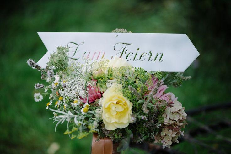 Ein Schild weist zur Hochzeitsfeier. Das Bild ist Teil eines rustikal-romantischen styled shoots der Hochzeitsfotografen Ladies und Lord aus Österreich.