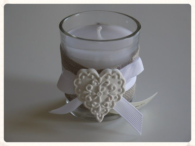 A rose water scented glass candle wrapped with fabric and a white ceramic heart attached with white ribbon These could be used as decoration at your