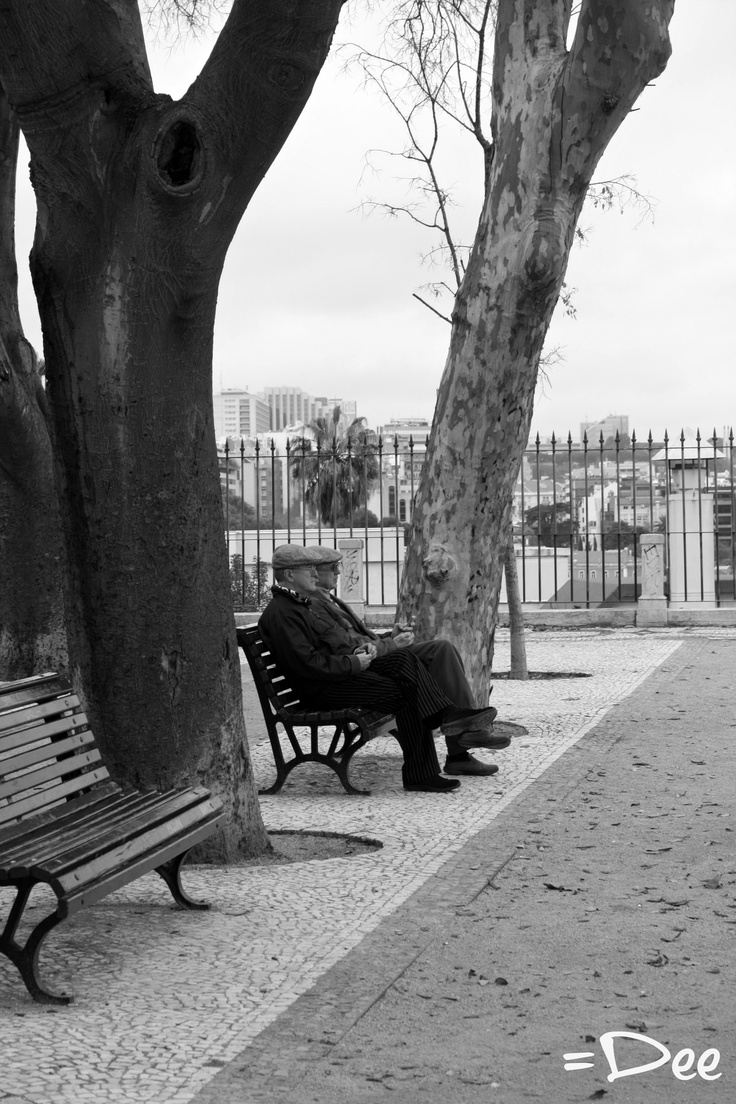 Two old men sitting in a park looking at the beautiful view of Lisbon
