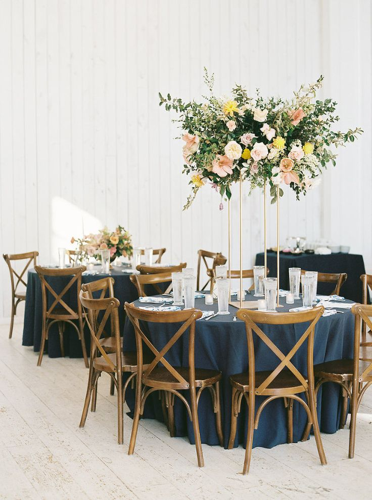 tall pink and yellow centerpieces on gold metal stands with crossback chairs at a wedding at The White Sparrow Barn.  Planned and designed by Birds of a Feather Events. To see more from this wedding, click here: http://birds-of-a-feather-events.com/white-sparrow-barn-wedding-melissa-thomas/