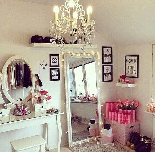 beauty corner. white bright vanity and chandelier. tall mirror