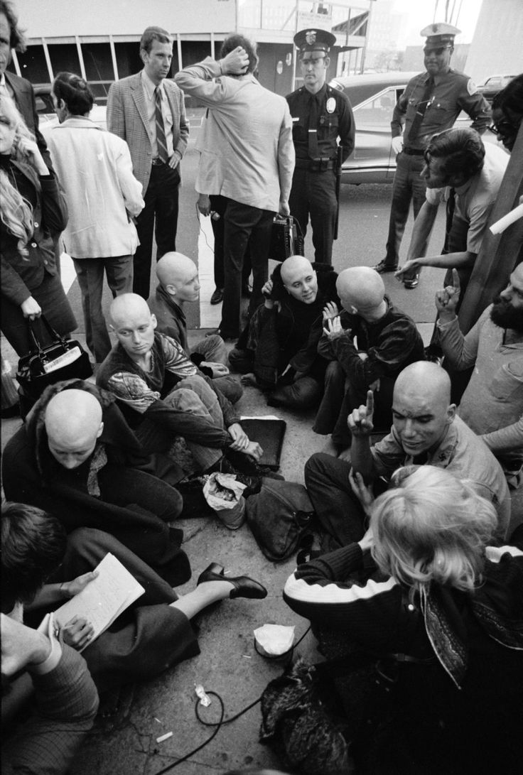 Followers of Charles Manson sit on the ground and speak with reporters outside of the courtroom where the Sharon Tate murder trial was being held in Los Angeles, California in 1971. During the trial, Manson, Patricia Krenwinkel, Susan Atkins and Leslie Van Houten all shaved their heads, which sparked followers to do the same.