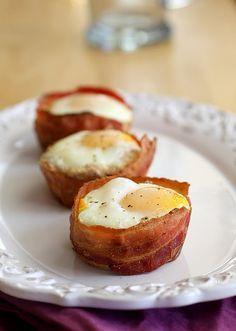 Copas Eggy! cortar el círculo de rebanada de pan, con cortador de galletas o beber vidrio; envuelva trozo de tocino por fuera de pan, colocar en molde para muffins engrasados. espolvorear el queso rallado con pan, cubra con un huevo. cocer en el horno hasta que el huevo es la forma que desee y el tocino esté crujiente.