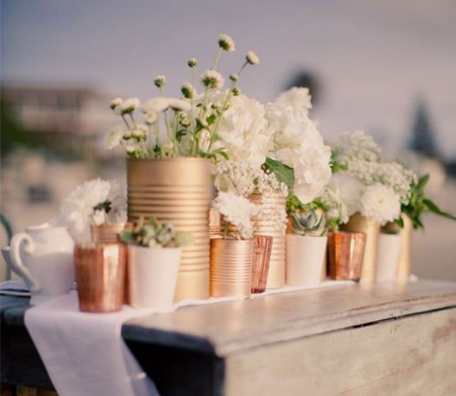 Spray paint some tin cans, throw in a few flowers, and you've got an amazing centerpiece.