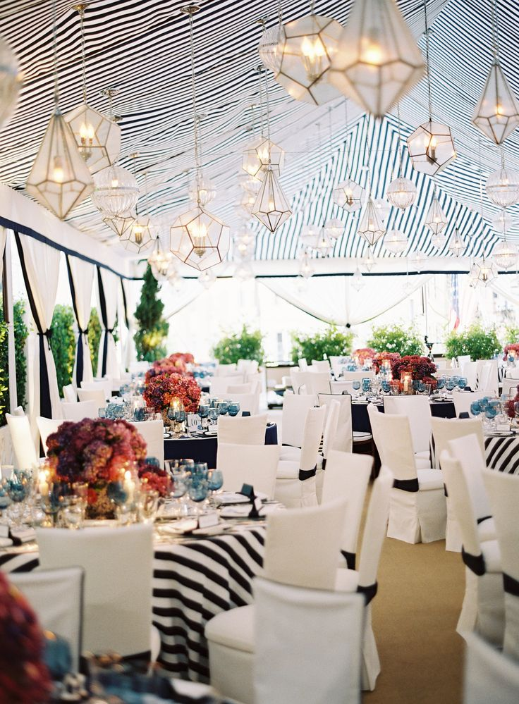 Guests were seated at round tables beneath a navy-and-white striped tent. Geometric glass vessels in different shapes were illuminated and suspended from the ceiling. #BlackandWhite #WeddingDecor Photography: Jose Villa Photography. Read More: http://www.insideweddings.com/weddings/incredible-rooftop-rehearsal-dinner-with-striking-striped-tent/555/