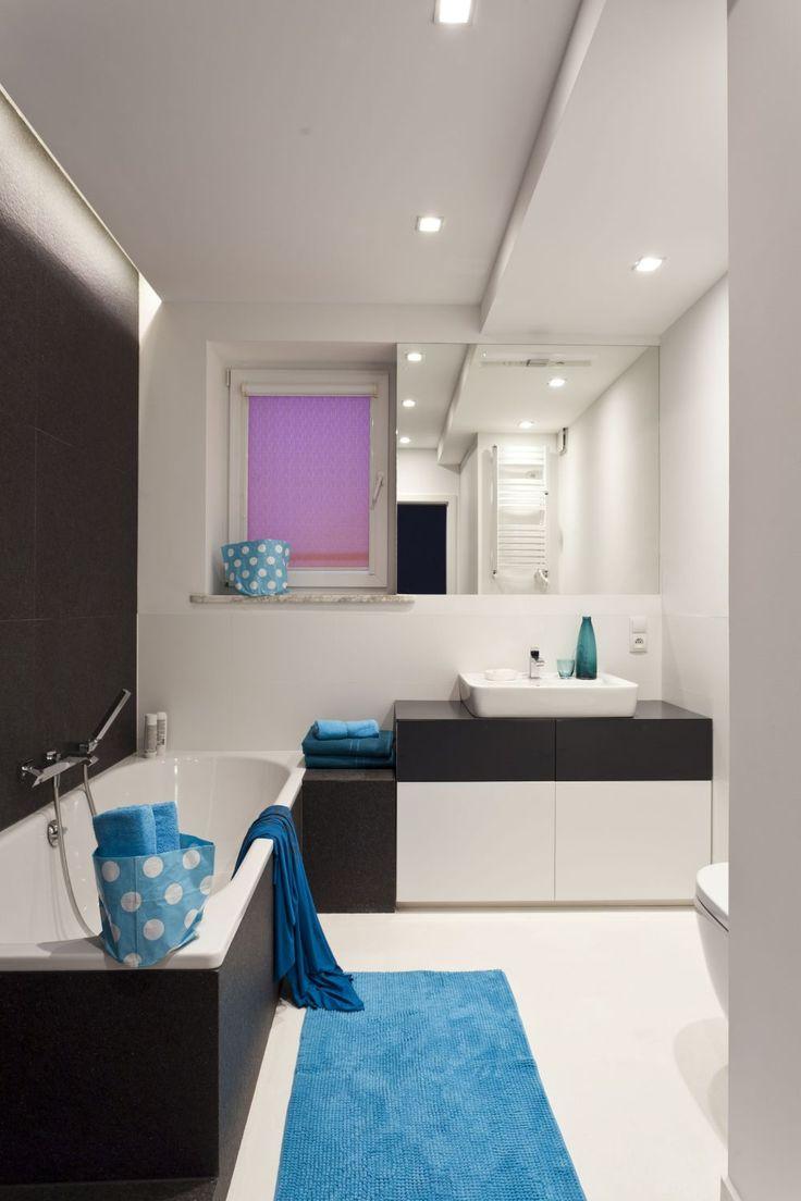 Łazienka w bloku jest elegancka i utrzymana w kolorze bieli i grafitu. Charakter wnętrza tworzą dodatki, a projekt łazienki zakłada, że można je dowolnie zmieniać. Błękitne akcenty przełamują monotonię kolorystyczną i ożywiają wnętrze łazienki w bloku.