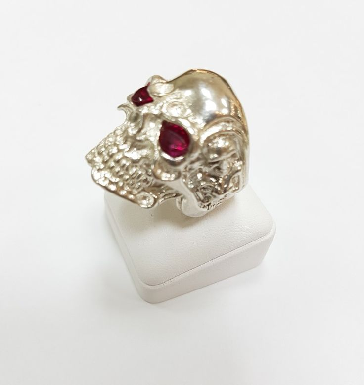 Sterling silver skull ring with two faux rubies gemstones.