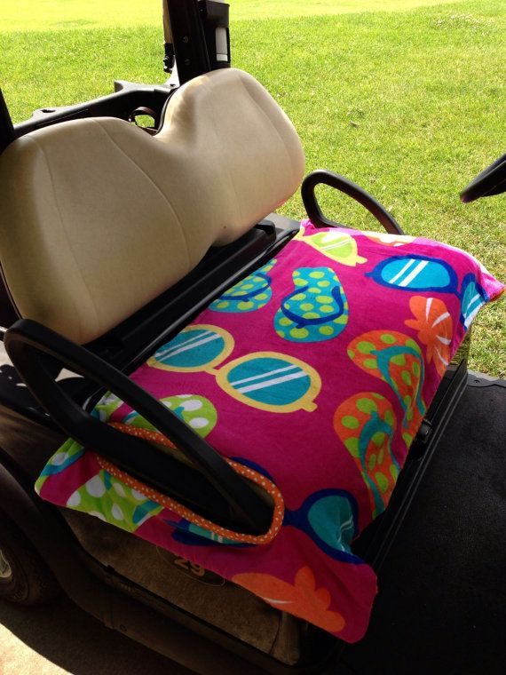Beach Essentials Golf Cart Seat Cover Front Side: Sunglasses & flip flops on pink background (terry fabric) Back Side: Solid Orange (terry) Handle Openings: Orange with white dots Features: Reversible, top & bottom are both terry, providing extra comfort and insulation, machine washable & dry-able, the weight of the double layers of terry cloth, prevents the seat cover from blowing off the cart in the wind. Size: Fits all U.S. single-seat golf carts Made in U.S.A. Price: $42.00