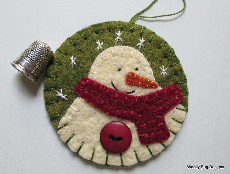 Ivory Wool Felt Snowman with Button and Handstitched Snowflakes on Green Wool Felt Ornament. $12.00, via Etsy.