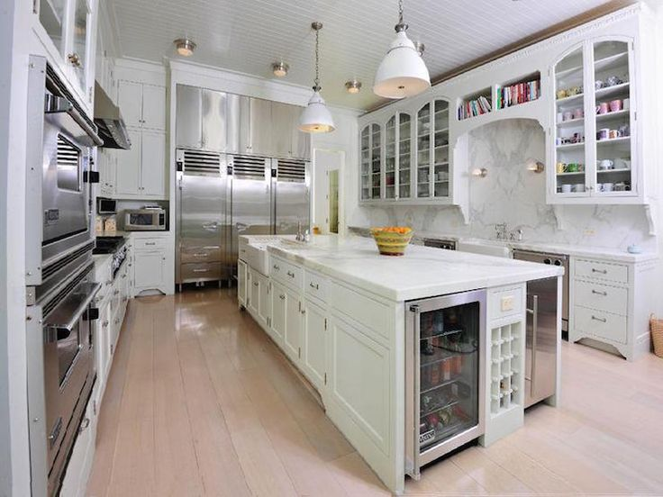 Huge kitchen features glossy white beadboard ceiling dotted with modern white pendants illuminating an extra-long island fitted with built-in wine rack flanked by a glass front beverage fridge to the left and a stainless steel mini fridge to the right topped with honed white marble countertop framing a farmhouse sink situated across from three counter depth industrial refrigerators and freezer drawers.