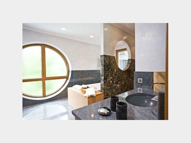 Badezimmer mit raumhohem runden Fenster aus Milchglaus (opakes Weißglas), das lichtdurchlässig, aber undurchsichtig ist. Außerdem besticht der Raum durch Granitverkleidung an Waschbecken und Wänden und verleiht edles, luxuriöses Flair. Gefunden im #Bauhaus Tessin auf haus-xxl.de