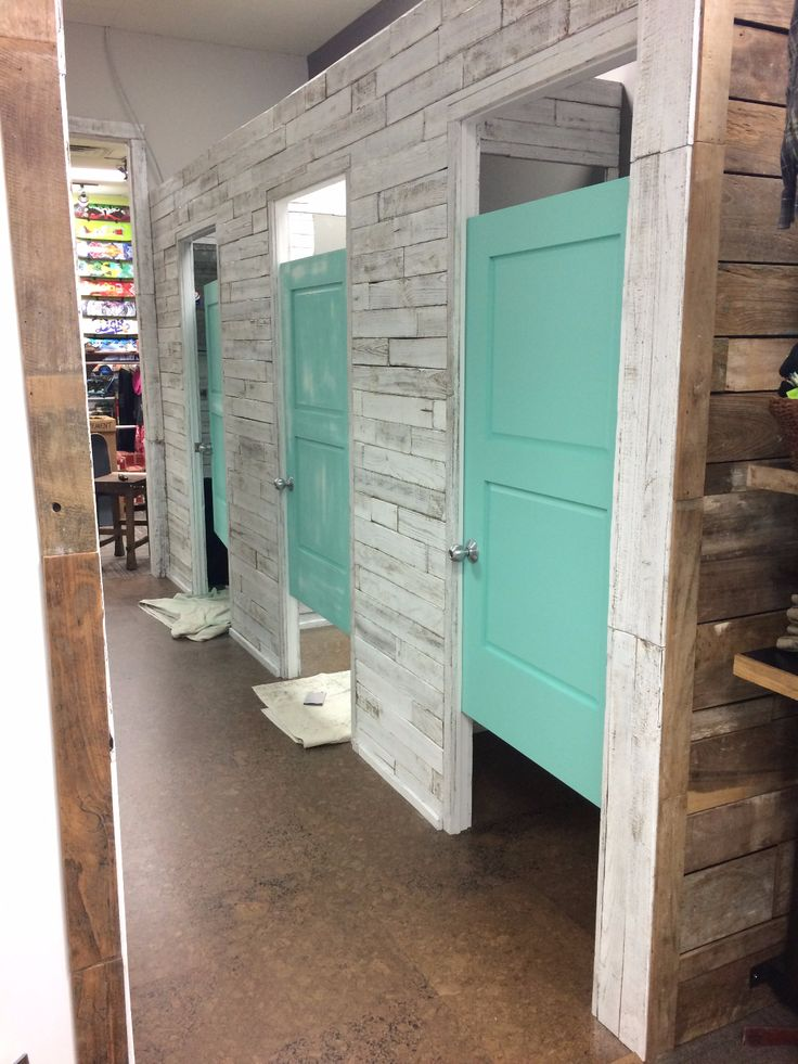 Reclaimed wood wall and dressing rooms at Sunrise Surf Shop in Jacksonville, FL. Iconic surf shops know where to find vintage wood! Salvage Whitewood finish.