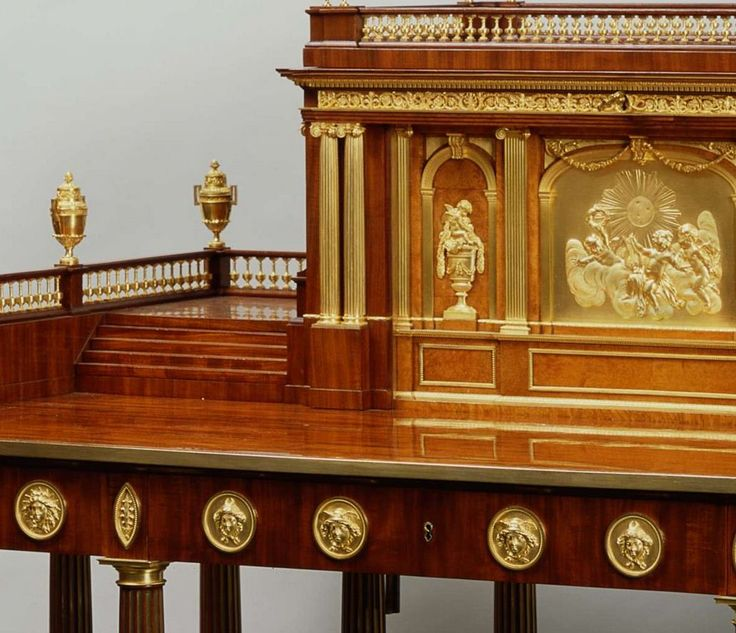 The large rectangular mahogany top, rimed by a plain gilt bronze band, rests on twelve tapering fluted mahogany and brass Doric columns linked by a U shaped solid wood stepped base. The bases and capitals of each column are with gilt bronze moulds chiselled with thin gadroons. The apron opens with three drawers and is applied with circular gilt bronze medallions chiselled with masks figuring alternatively Mercury, the Moon and the Sun and with lozenge medallions chiselled with stiff leaves.