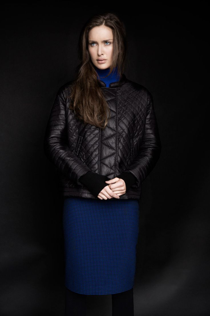 Black padded jacket paired with blue fitted skirt, both Carolyn Donnelly The Edit