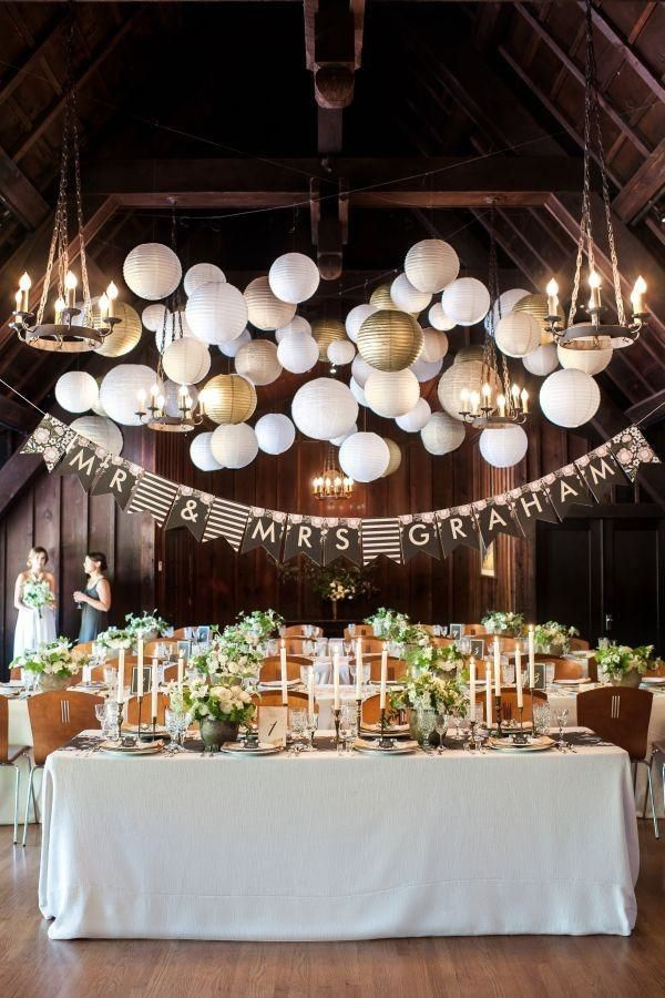 White and gold paper lanterns, mismatched bunting newlyweds sign and elegant floral centerpiecs at an indoor lodge wedding reception.