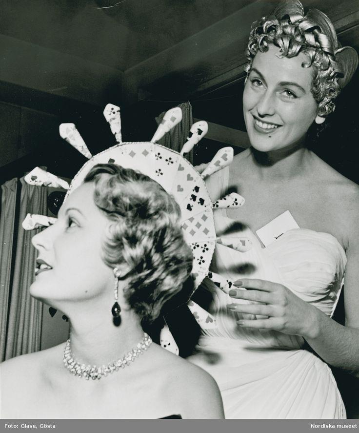 En kvinna med hatt av kortlek, örhänge och halsband, framför kvinna i vit aftonklänning med spelkort vid dekolletaget. Fotograf: Gösta Glase, ca 1950-1959