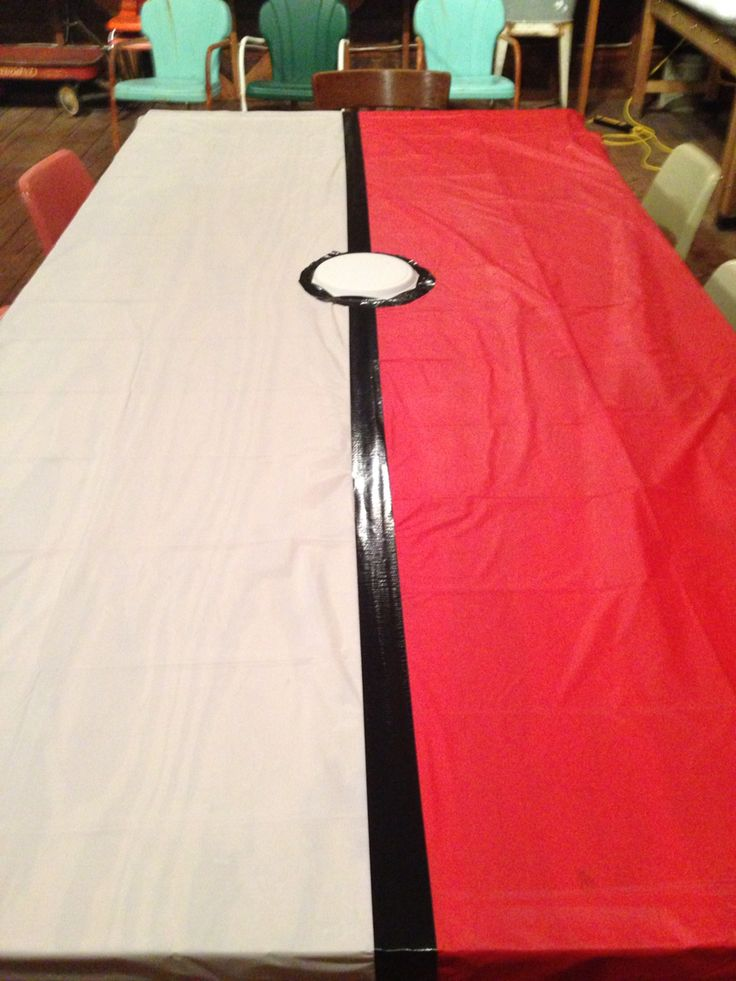 My DIY Pokemon party table covers. $1 store white plastic table cover, red plastic cover, black duct tape, and a paper plate. I folded the table covers in half, then taped them together with the duct tape. I put more duct tape around a paper plate to make the button, but they looked fine without the button also.