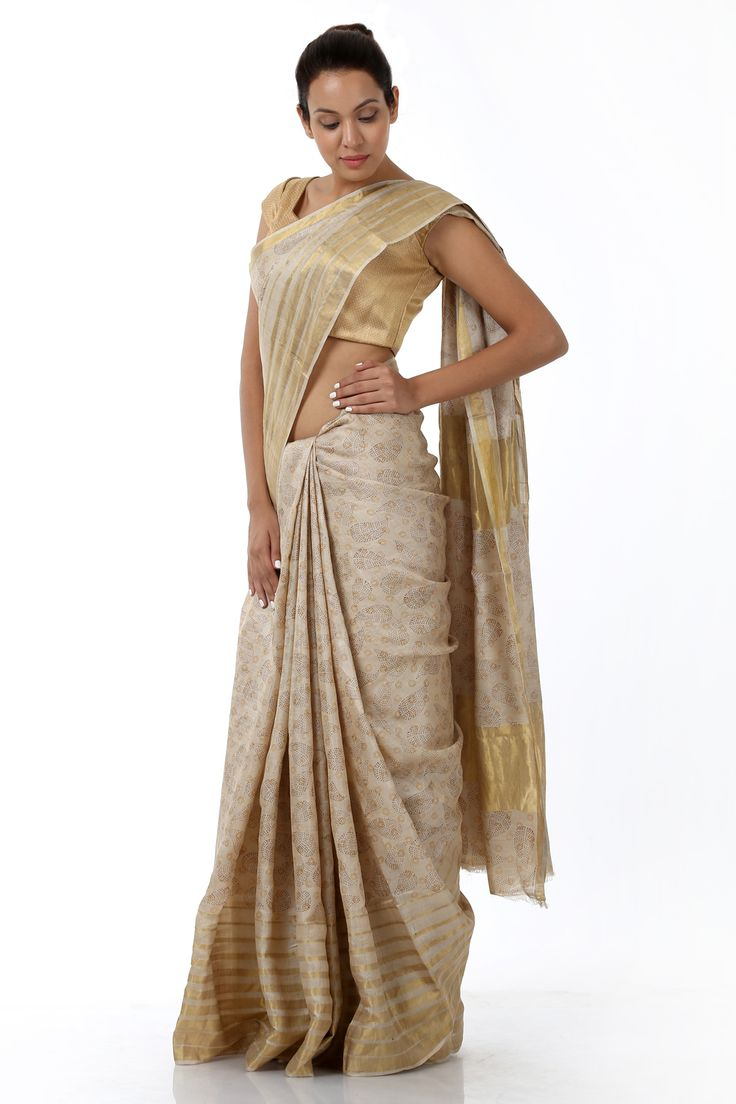 An off-white kosa silk sari, luxuriously designed with intricate patterns all over the silhouette. This designer creation is enhanced with contrasting golden border and is made desirable with a simple yet engaging outlook. It comes with a complimenting blouse piece.
