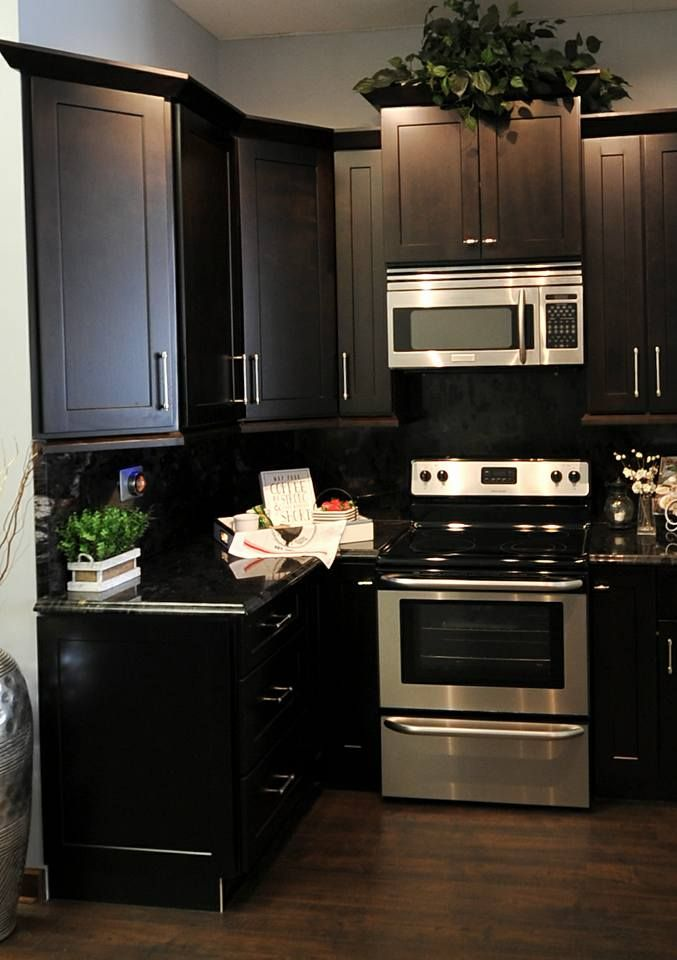Espresso cabinets with dark countertop that runs up as ...