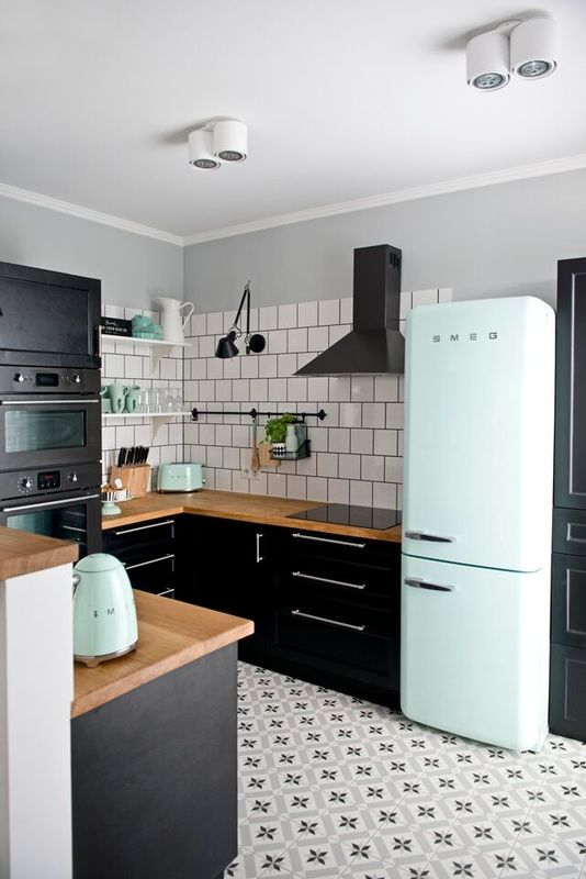 Beautiful kitchen with black cabinets, white square tiles, patterned floor tiles and pale mint SMEG accessories