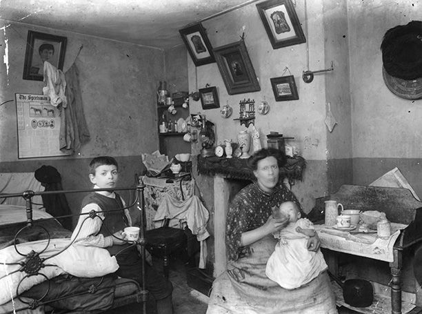 A mother with her baby and child in a typical London slum, December 1912. The bedroom also serves as a kitchen. Getty Images/Hulton Archive