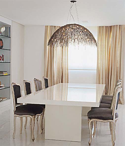 mesa neutra e de linhas contemporâneas e cadeiras de estilo clássico