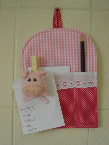 /Porta recado feito em tecido 100% algodão estruturado com manta acrílica especial para patchwork com espaço para a caneta/lápis e para o bloquinho de papel. Acompanha prendedor com porquinha feita com feltro e enchimento, para prender o recadinho.  **Acompanha bloquinho e lápis preto** **Medida não inclui a argolinha de pendurar** R$ 15,00