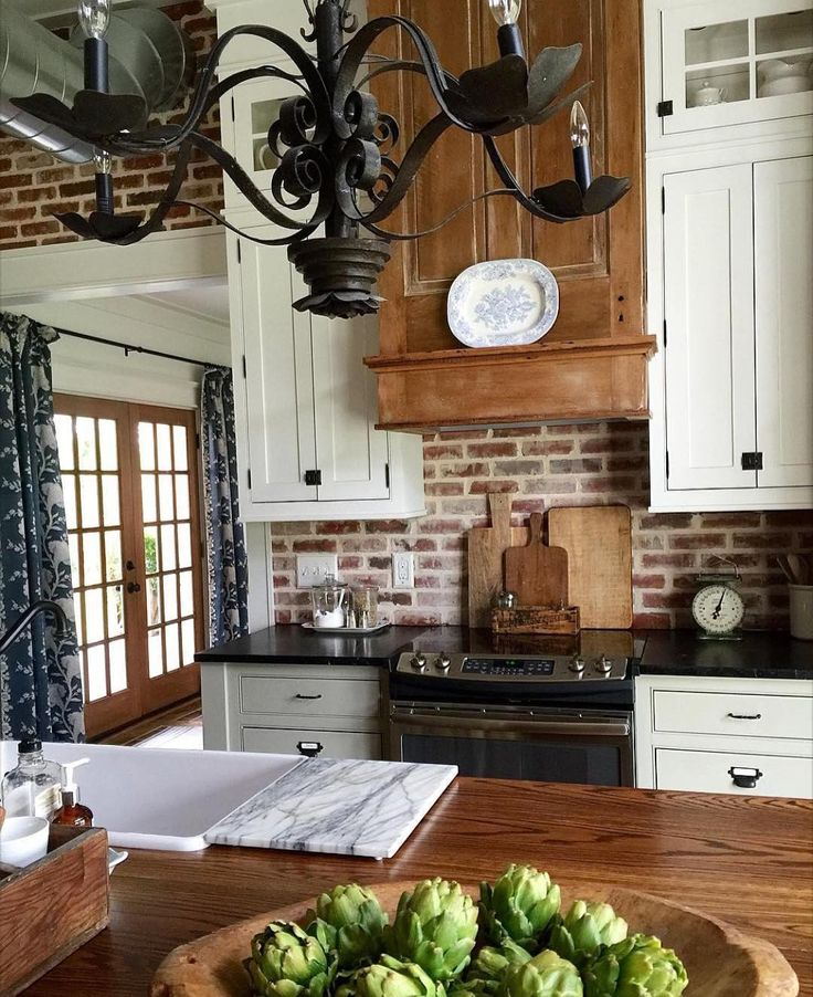 Gorgeous kitchen! Tall ceiling, brick wall, iron chandelier, wooden cutting boards, white cabinets, rustic wood, and an antique scale to boot.