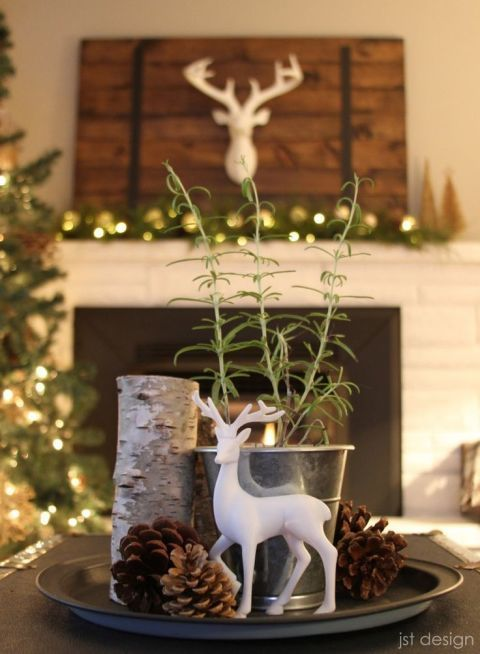 A small white deer stands out beside rosemary, pinecones, and birch bark candles. See more at JST Design.