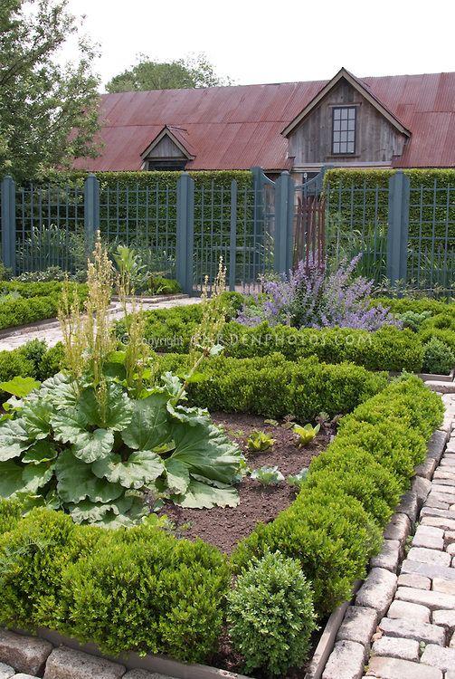 upscale vegetable garden with cut stone walkway fence trellised
