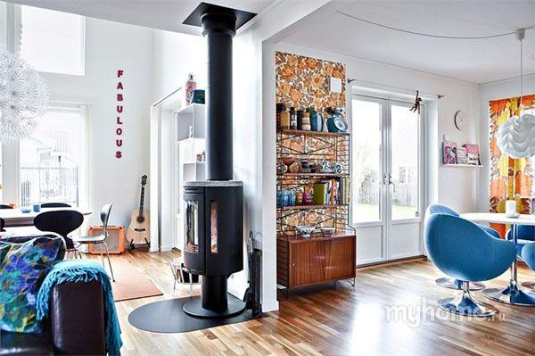 Современная гостиная выполнена в сочетании белого и коричневого цветов с контрастом синих оттенков. Отдельно вынесенное рабочее место в зоне кухни обеспечит комфортное приготовление пищи. Встроенная техника экономит много свободного места. На фартук уложена коричневая керамическая плитка. Яркими акцентами в помещении являются голубые стулья. Освещение представлено в виде подвесного светильника. На пол уложен ламинат.