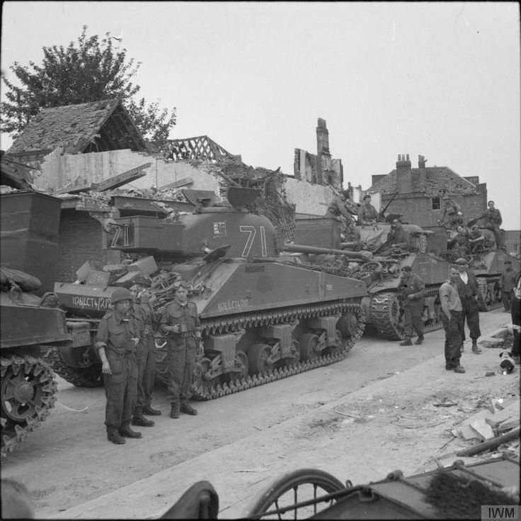 A Sherman Firefly and Sherman tanks of 'C' Squadron, 13th/18th Royal Hussars waiting to be loaded aboard landing ships at Gosport, 3rd June 1944. The Firefly crew in the left foreground are Trooper Fred Shaw, Trooper Doug Kay, Sergeant Fred Scamp and Trooper Bill Humphries. Their vehicle was named 'Carole'.