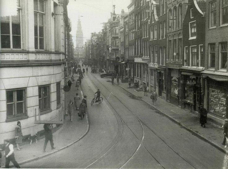 1930 Jodenbreestraat  Tot 1893, toen Joodse straat- en markthandelaren op last van het stadsbestuur naar het Waterlooplein verhuisden, diende de straat, vooral op zondag, als marktplaats. De Jodenbreestraat lag midden in de 'Jodenhoek'. Deze Joodse wijk lag tussen de Nieuwmarkt, de Kloveniersburgwal, Raamgracht, Waterlooplein, Weesperstraat, Muiderstraat, Nieuwe Herengracht, Rapenburg en Uilenburg.