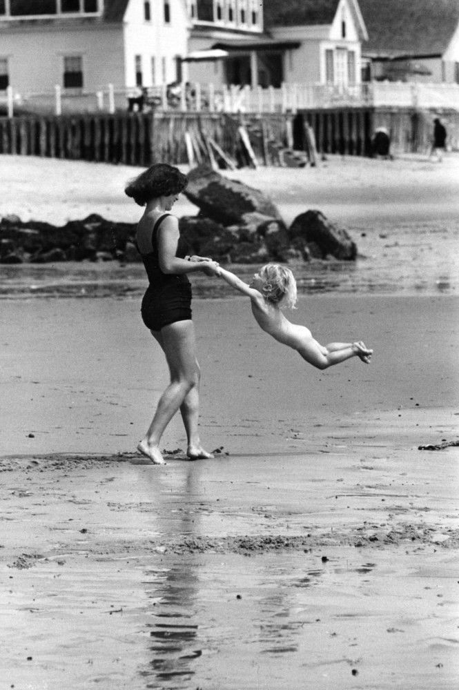 A mother plays with her child on the beach. [c. 1950s]