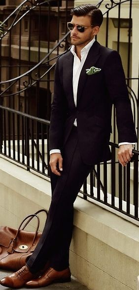 Classic Black Slim Fit Suit, Crisp White Shirt, Tom Ford Sunglasses, and Tan Leather Bag. Men's Spring Summer Fashion.