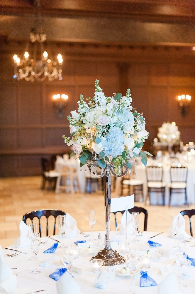 A tall table centerpiece with floral pastels and blue and white hydrangeas at an indoor wedding reception | Leslie Ann Photography | villasiena.cc
