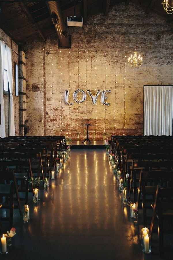For an industrial wedding venue, add some intimate charm using candlelight. With decorations like the balloon sign and string lights, this wedding seems very contemporary. But simple candles and greenery lining the aisle create a more rustic vibe to a modern wedding.