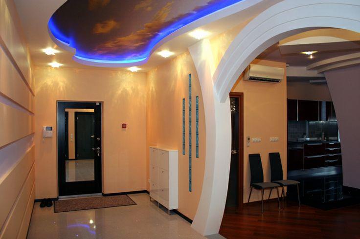 Прихожая. Основной изюминкой этой квартиры являются потолки. Это и сложный по конструкции, выполненный из гипсокартона потолок в зале, и очень эффектные натяжные потолки в коридоре, спальне и лоджии, представляющие собой небо с плывущими облаками в разное время суток. Здесь и рассвет, и полдень, и пламенеющий закат.