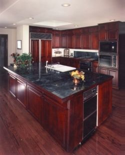 My dream kitchen...black granite countertops with cherry wood cabinets and black appliances <3