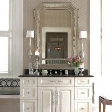 This master bathroom is beautifully appointed with a decorative marble tile border, granite countertops, a free-standing vanity and unique mirror-framed mirror and sconces.  Who wouldn't want to get ready every morning in this bathroom? Designed by Pulliam Morris Interiors