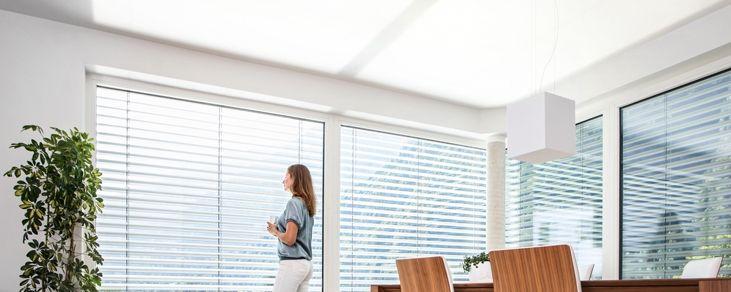 Intelligenter Raffstore statt Klimaanlage und Kunstlicht  Das kennt jeder, egal ob von zuhause oder aus dem Büro: Draußen 30 Grad und Sonnenschein – das heißt Fenster verdunkeln, Licht ein, Klimaanlage an. Und so verbringen viele Menschen den ganzen Tag mit künstlichem Licht, laufender Klimaanlage und ohne Sicht nach draußen. Das ist nicht gesund, nicht besonders angenehm und kostet zudem jede Menge Geld. Wir haben die Lösung: den Tageslicht-Raffstore RETROLux.