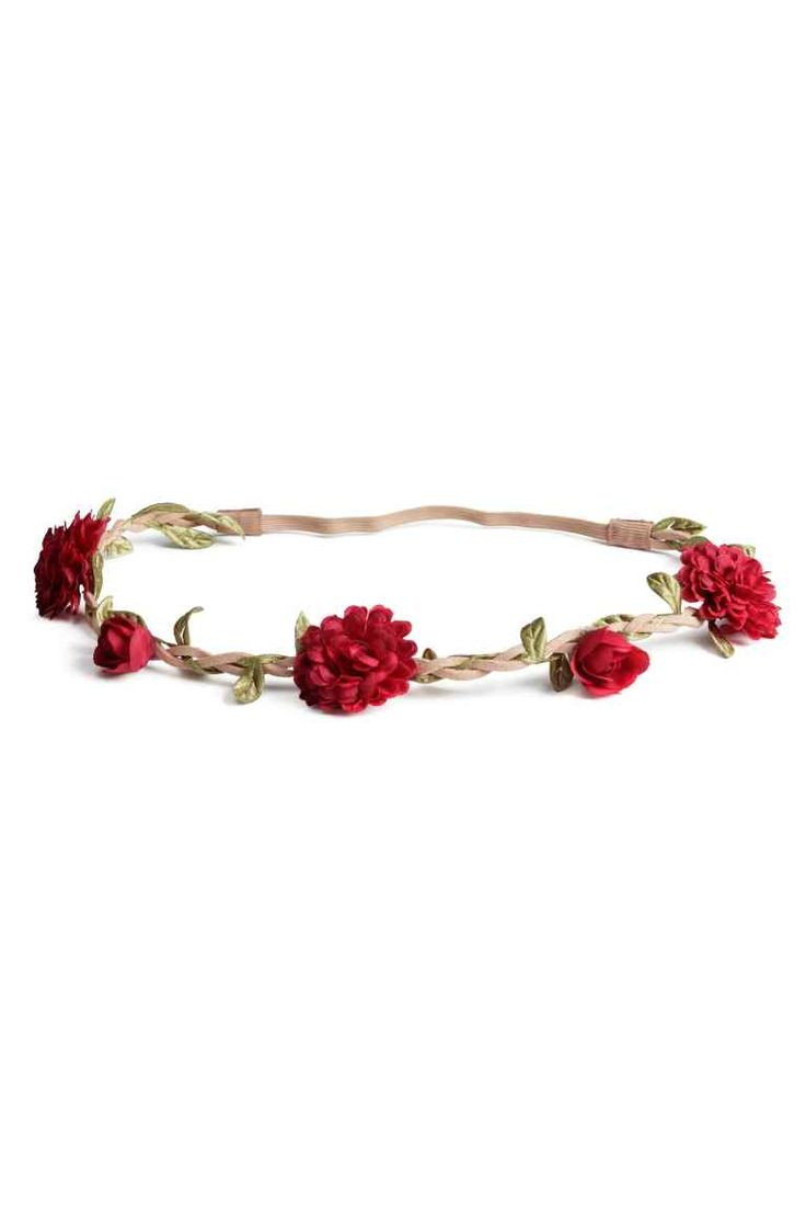 Fita de cabelo com flores: Fita de cabelo entrançada em camurça sintética com aplicação de flores e folhas e elástico atrás.