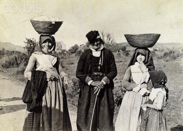 Women and children with baskets on their heads travel a village road - Sardegna 1916 #TuscanyAgriturismoGiratola