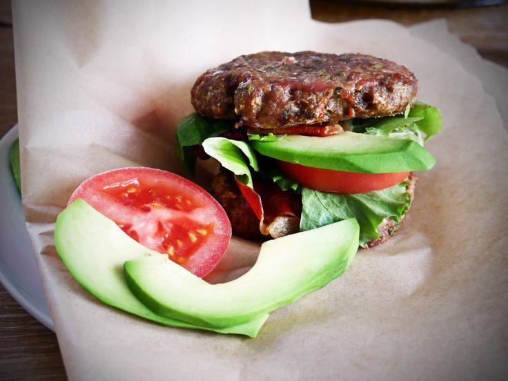 Burger drobiowy bez bułki  Składniki (porcja dla 2 osób):      chude mięso mielone drobiowe 400 g     1 cukinia     1 por     ½ cebuli     pół pęczka koperku     pół pęczka pietruszki     szczypta pieprzu     olej kokosowy lub masło klarowane     szczypta soli morskiej     szczypta cayenne     szczypta kolendry  Dodatki:      1 awokado     1 pomidor duży     liście sałaty