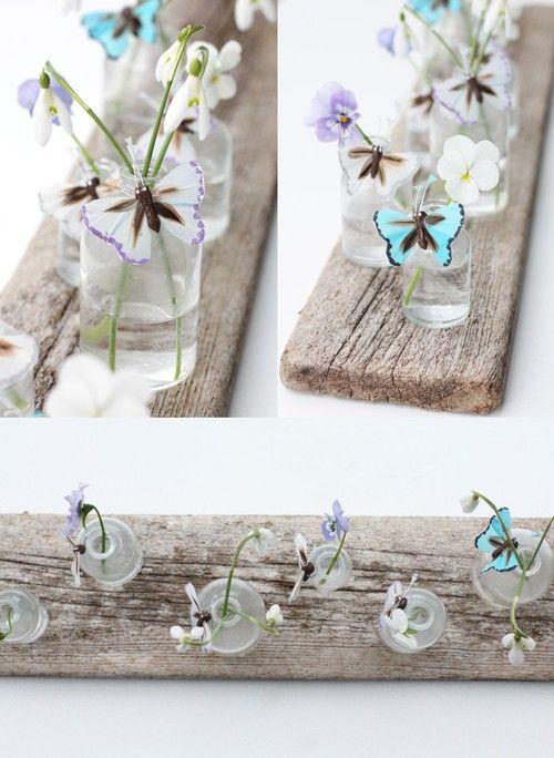 plank voorzien van glazen vaasjes (erop gelijmd?) en bloemetjes. dat schuift gemakkelijk aan de kant